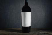 A single Merlot bottle, white label